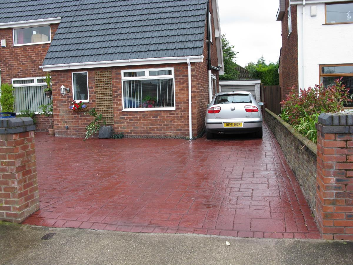 Concrete driveway stamped with ashlar slate and mews cobblestone edging and finished in satin cortez red for property in Lytham St Annes.