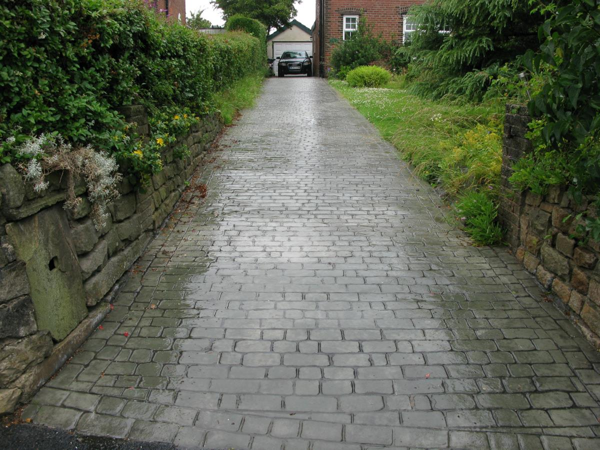 Mews cobblestone effect textured concrete coloured in green stone and with a gloss finish, installed to a long sloped driveway in Ormskirk.