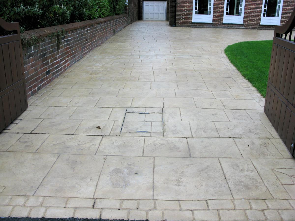 Pattern imprinted concrete driveway stamped to resemble stone flags with mews cobblestone edging for household in Chorley.