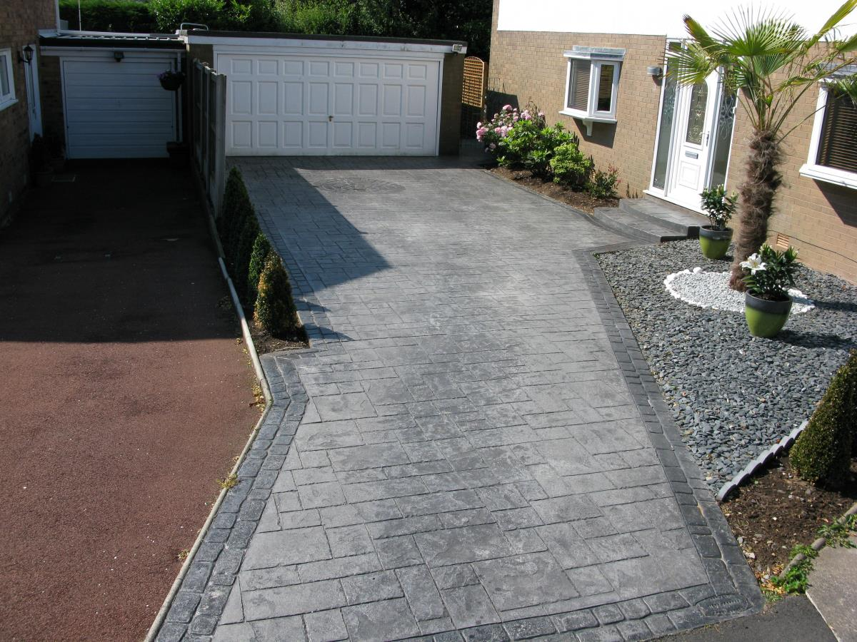 Pattern imprinted driveway in Leyland in basalt grey ashlar slate, with stone grey cobble edges.