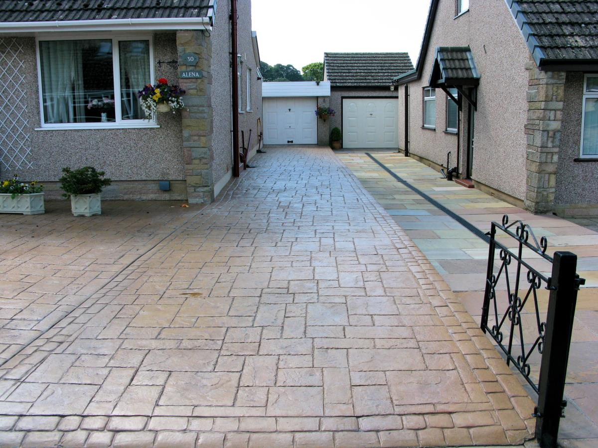 Pattern imprinted driveway textured in ashlar slate and coloured in country sandstone for bungalow in North West.