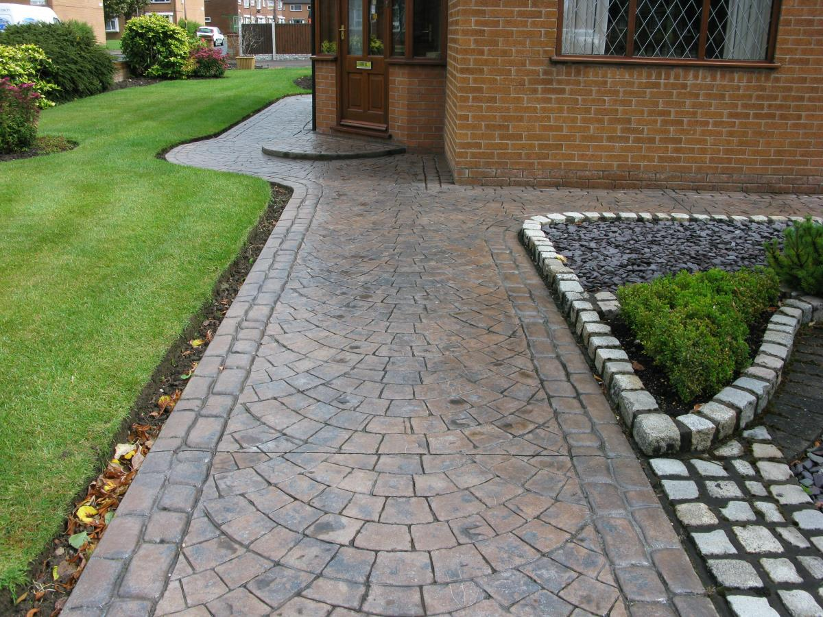 Patterned imprinted concrete path in toffee coloured European fan, edged with mews cobblestone for a house in Lancaster.