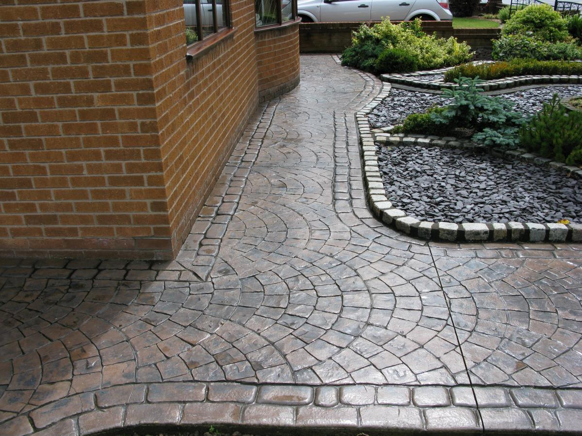 Toffee coloured concrete garden path textured with European fan and edged with mews cobblestone laid at a home in Ormskirk.