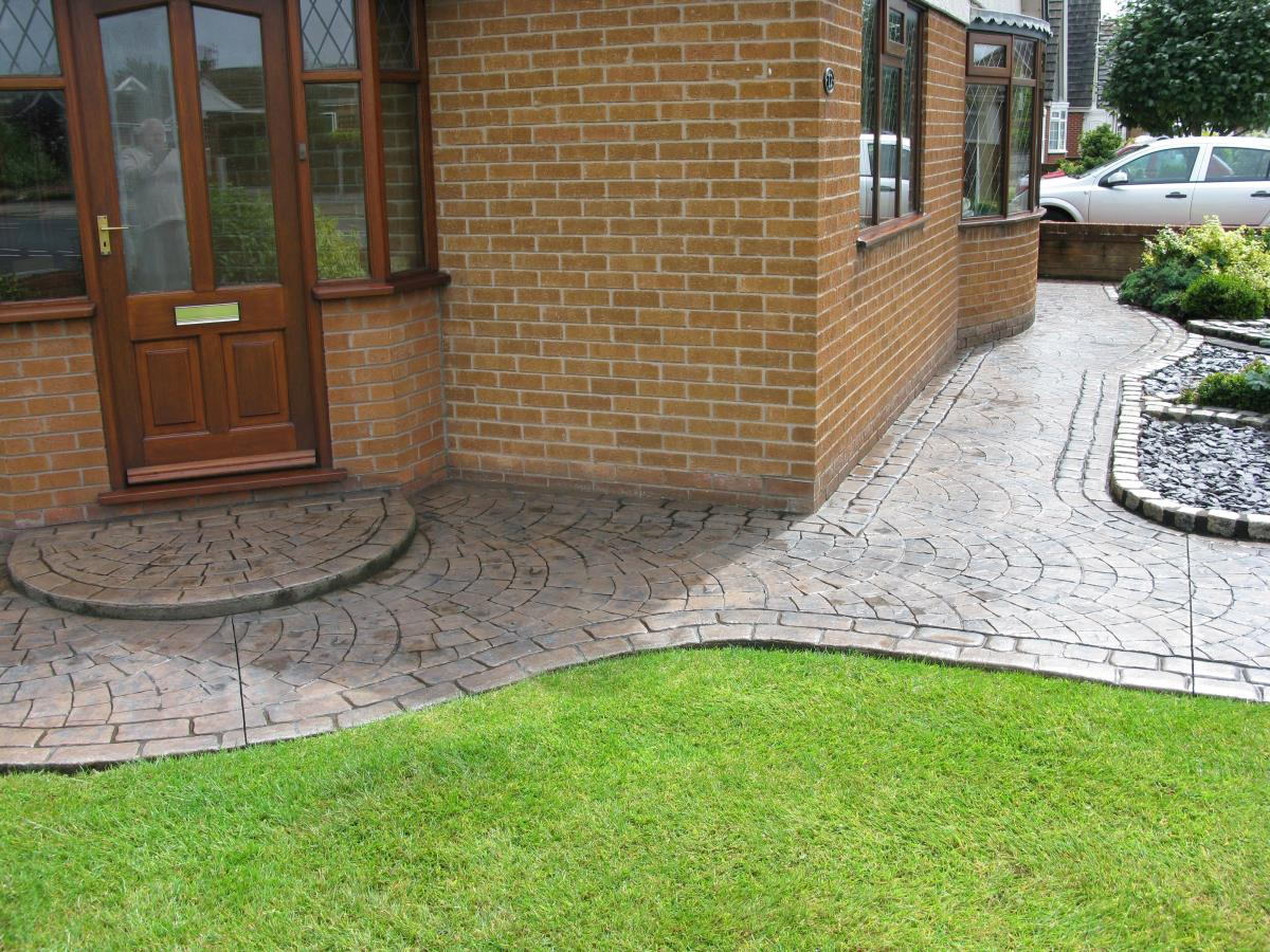 Toffee coloured concrete garden path textured with European fan and edged with mews cobblestone laid at a home in Bispham, Blackpool.