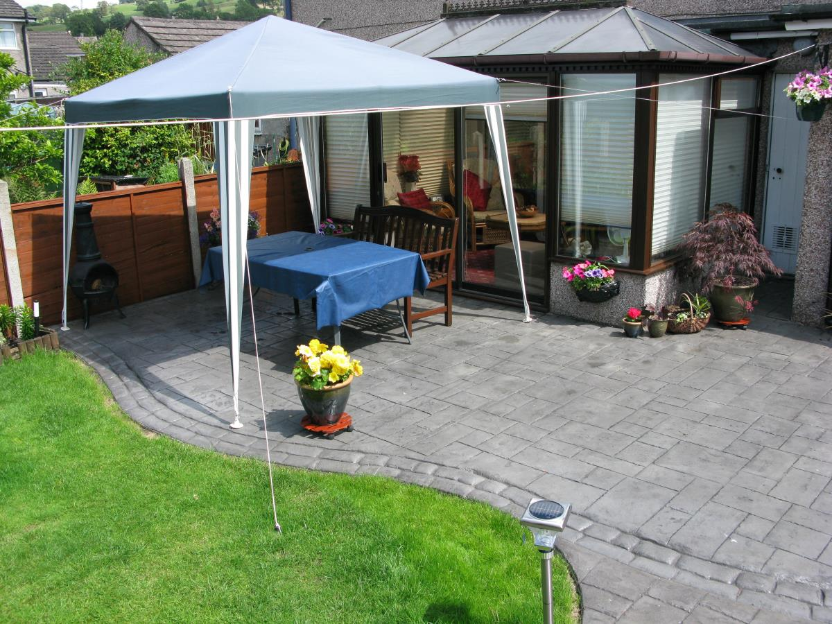 Concrete patio with satin finish stamped with ashlar slate and mews cobble edging in Warrington.