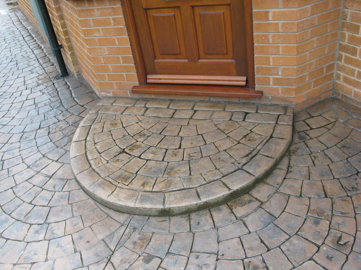 Semi circular European fan style concrete step edged with mews cobblestone, coloured in toffee with a satin finish for home in Lancashire.