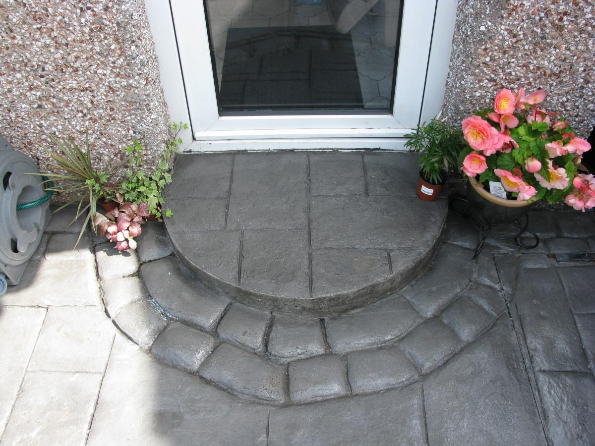 Semi circular silver grey coloured concrete step in ashlar slate style edged with mews cobble for Southport rear garden.